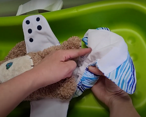 fitting cloth diaper onto baby - create u-shape with bulk of diaper between baby's legs