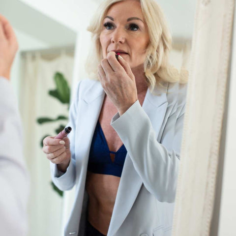 Woman confidently applying makeup on in her lingerie