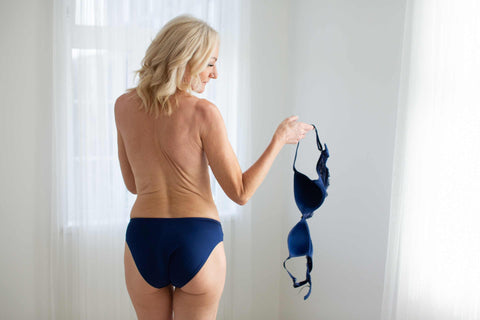 Woman with bra off holding her bra