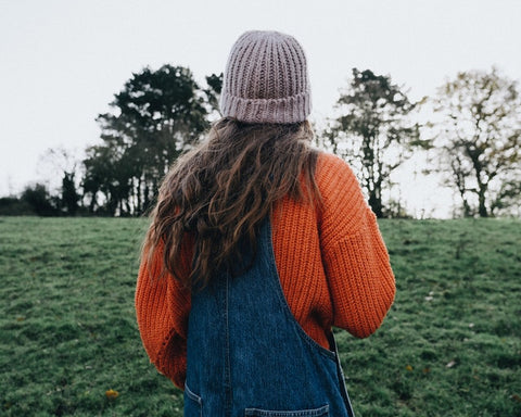Girl looking at horizon during the fall in a field.