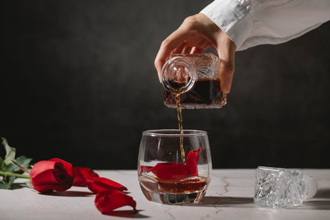 Someone pouring alcohol into a short glass with rose petals in it.