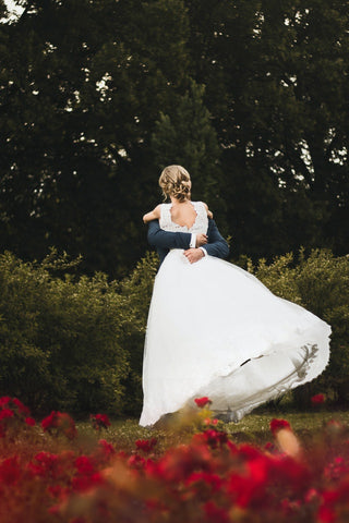 Woman in wedding dress getting carried by her husband on field.