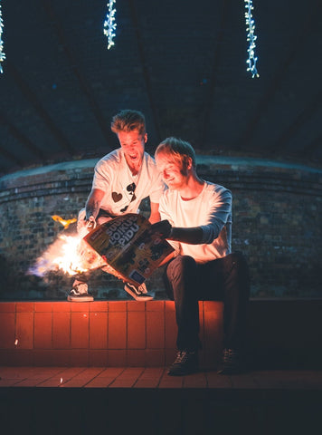 Two adults playing with fire and smiling.