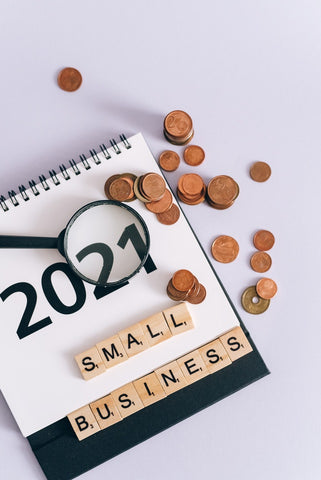 Small business spelled out in scrabble with a calendar in the background