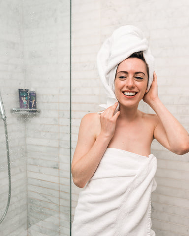 Woman in with hair in towel coming out of shower. Take time for yourself! That's a huge thing to do when it comes to self-love and self-care!