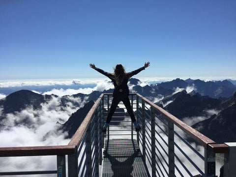 woman-jumping-in-freedom-with-mountain-view