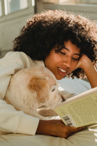 Woman in bed with dog reading a book