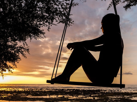 woman-sitting-on-swing-at-sunset-and-thinking