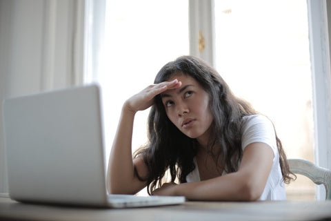 Woman unhappy with her job, as she sits in front of computer and rolls her eyes.