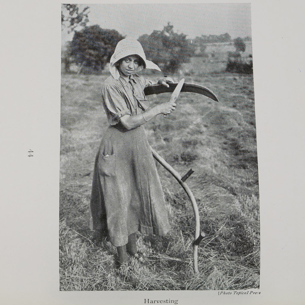 Black and white photograph of a white, dark-haired woman agricultural worker in a long dress and a shirt with the sleeves rolled up and with a white hat standing in a field and sharpening a scythe. She stands facing the right side of the image, but turns her head and smiles at the camera.