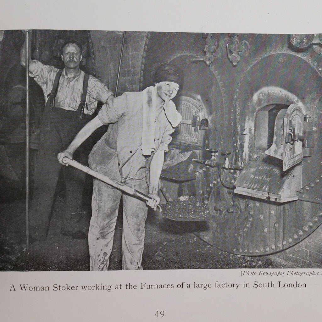 Black and white photo of a woman in overalls with her shirt sleeves rolled up and a handkerchief on her head shovels coal into a large, industrial furnace.