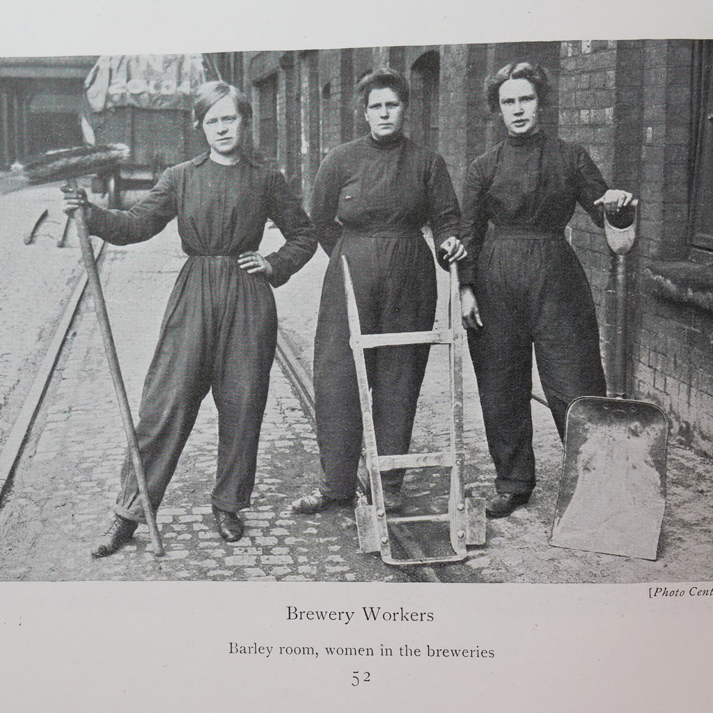 Black and white photo of three white women in dark coveralls and with their hair pinned up, standing in a street and holding brooms, a handcart, and a shovel.