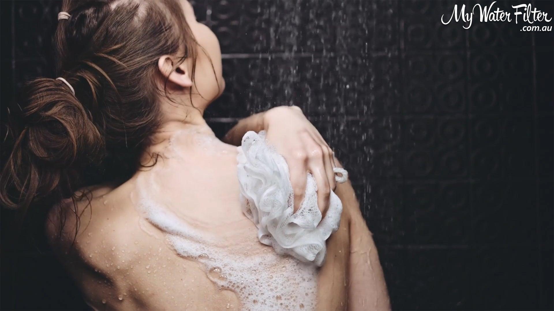 Lady scrubbing her back in the shower