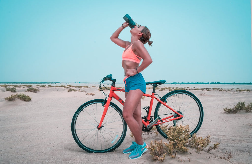 Woman drinking water on her bicycle