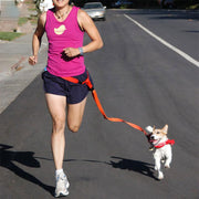 Person jogging with dog attached to the hands free pulling leash