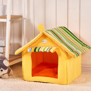 Yellow dog house bed with green striped roof