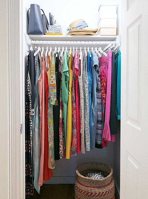Closet with brightly colored clothes hanging in it.
