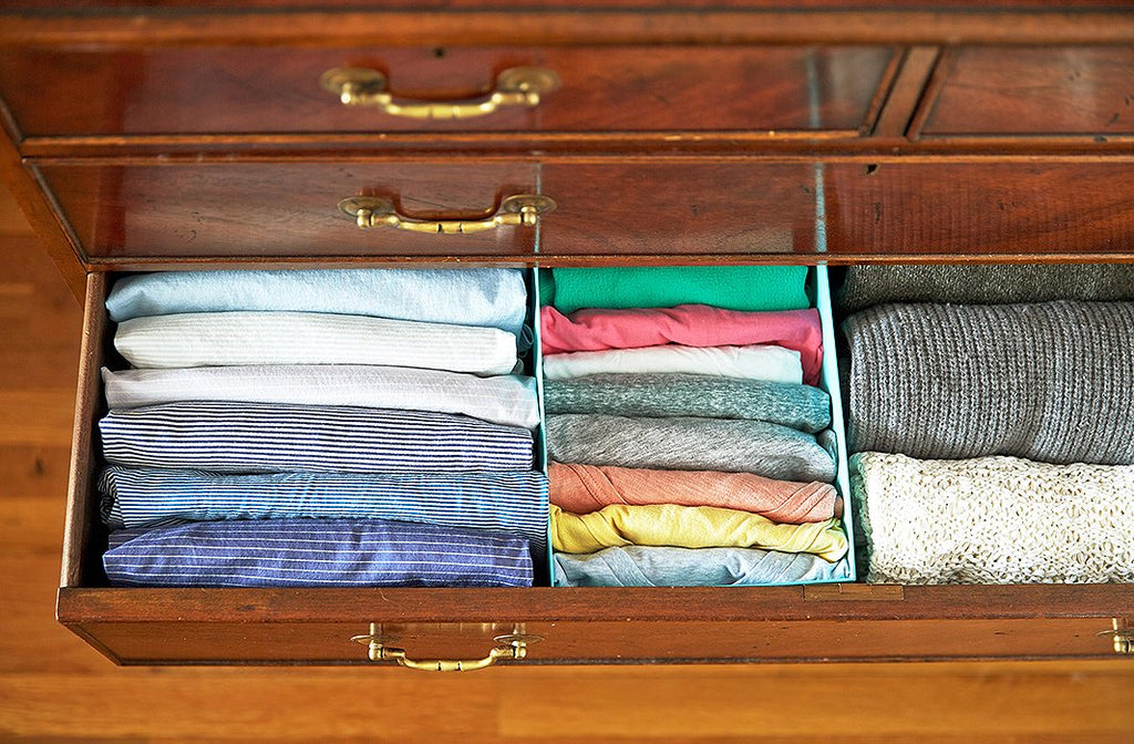 Drawer with brightly folded clothes showing.