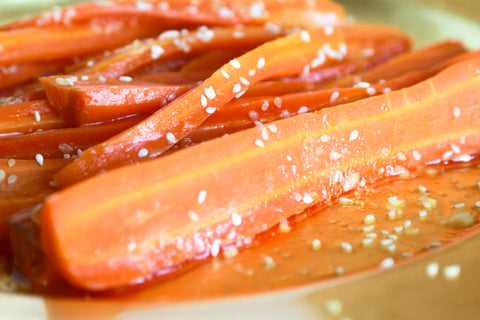 close up of roasted carrots topped with sesame seeds and honey
