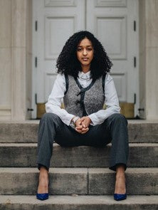 empowered woman sitting in business casual clothing and natural hair