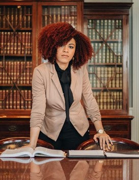 beautiful woman standing in library wearing business professional clothing and natural hair