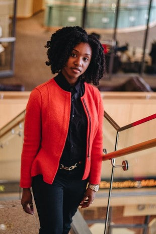 beautiful woman standing in ballroom wearing business professional clothing and natural hair