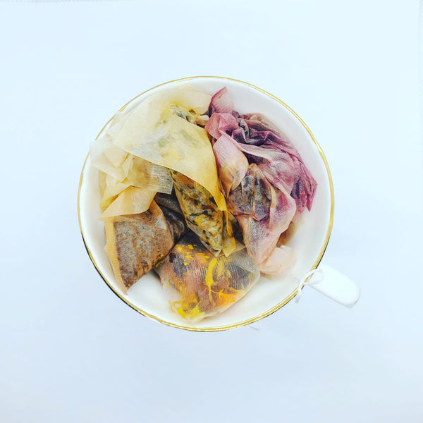 Vintage bone china tea cup with assortment of sampled tea bags in yellow, deep purple and rich browns