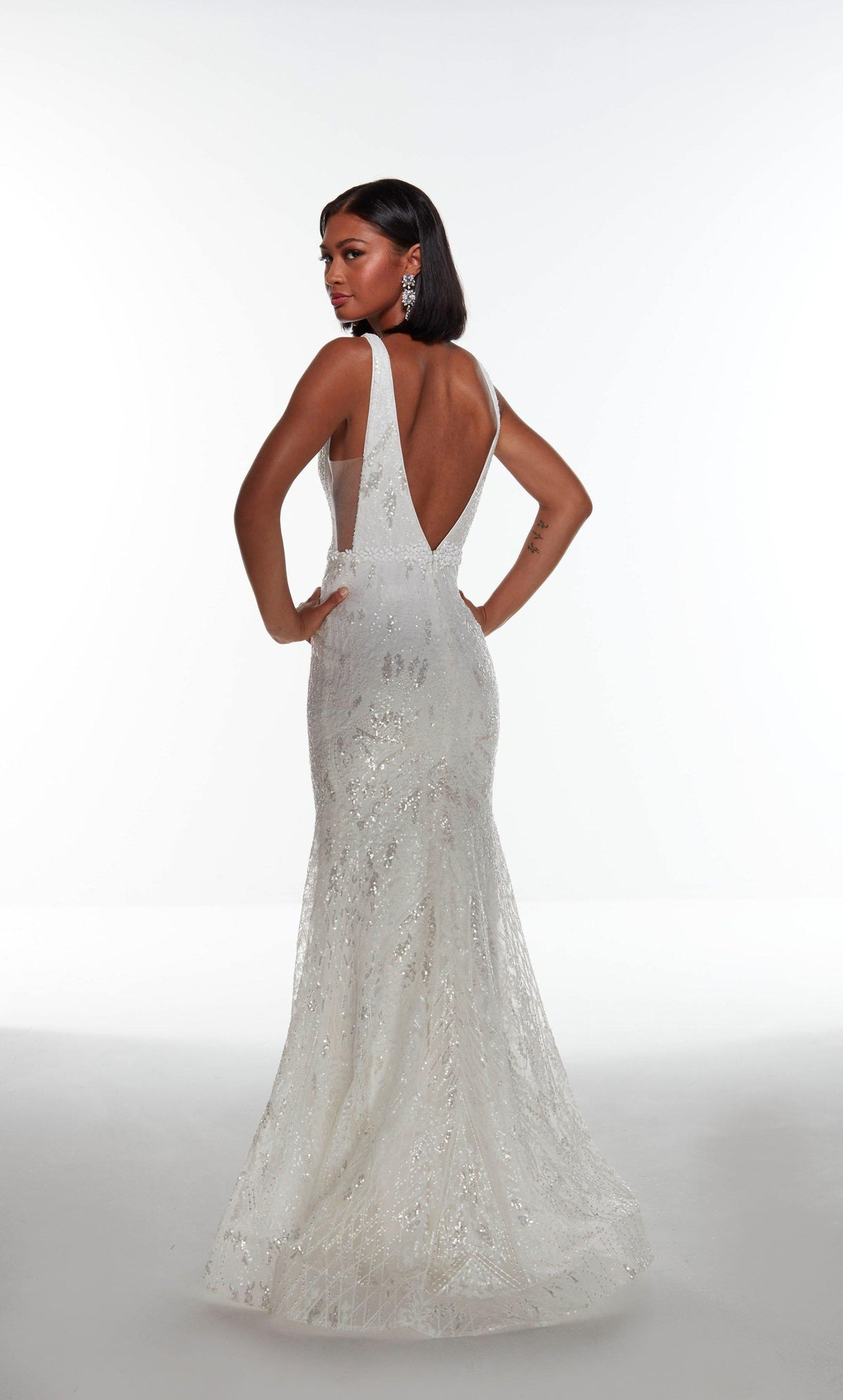 Fully sequin embellished Diamond White colored wedding gown with a V shaped back and a jewel accents at the natural waist