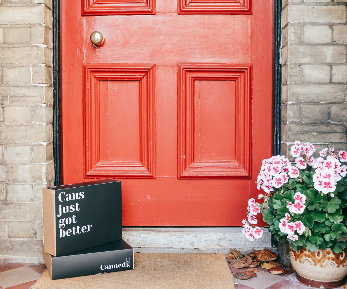 Canned Club alcohol subscription box on doorstep with red door and potted plant