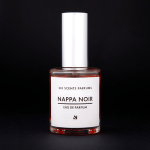 Bottle of Nappa Noir Perfume by SIX SCENTS PARFUMS in front of a black background