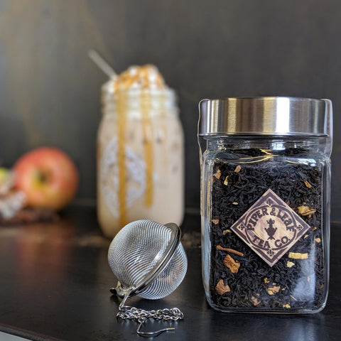 A loose leaf jar of Caramel Apple Pie and a tea ball. Further back is a jar of tea dripping with caramel drizzle.