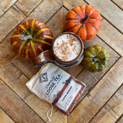 A bag of Pumpkin Moonshine tea and a mug filled with a cinnamon-sprinkled drink surrounded by small pumpkins