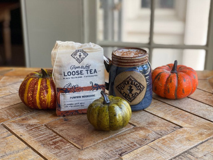 Pumpkin Moonshine loose leaf next to a mug topped with whipped cream and cinnamon. Behind them are three small pumpkins.