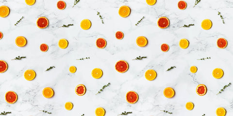 A collection of orange slices and herb sprigs across a marble countertop