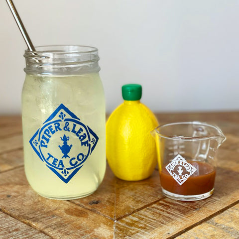 A pint jar of lemonade, lemon, and tiny measuring cup of tea concentrate
