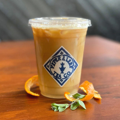 A cup of iced cold-brew coffee garnished with orange peel and a sprig of thyme