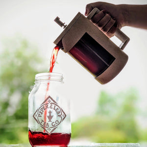 Pouring freshly brewed tea from a Piper Press into a Piper & Leaf quart jar