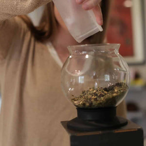 Pouring a full bag of loose leaf into a Tea Dripper strainer to make concentrated tea