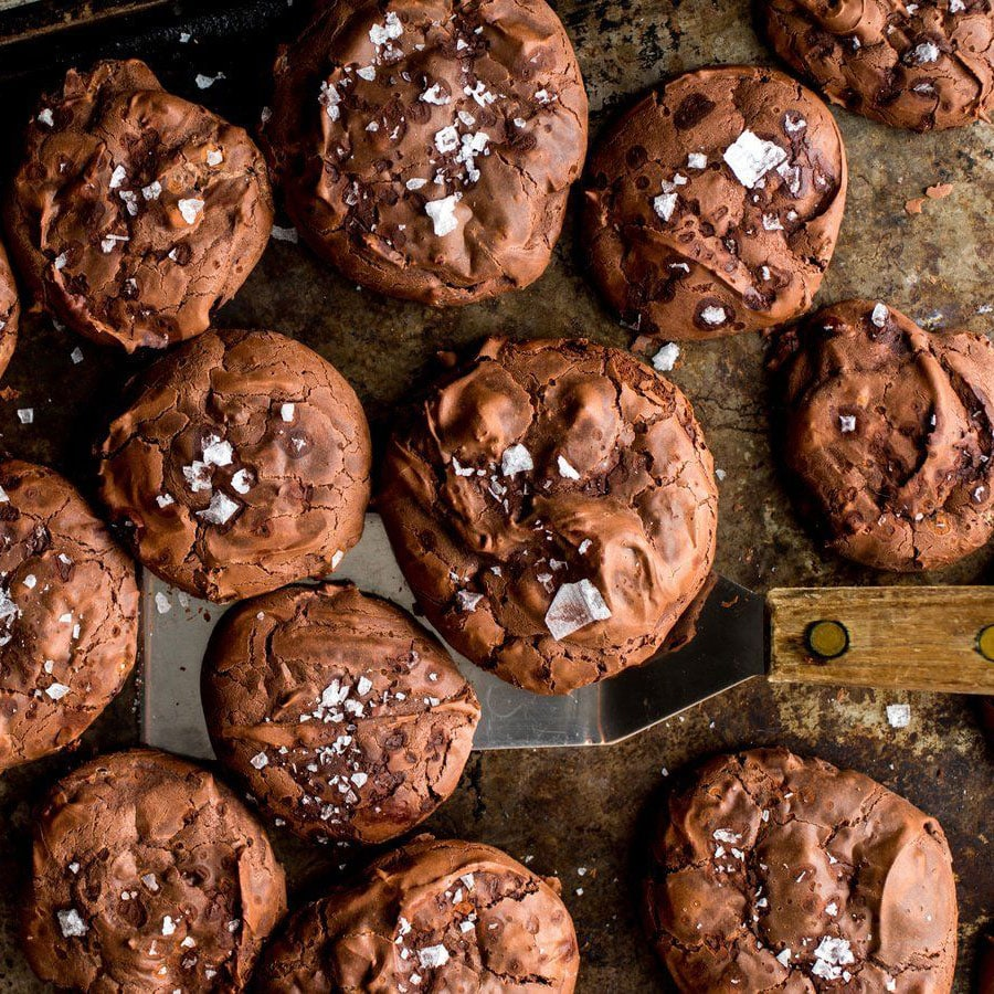 Freshly baked chocolate cookies being scooped off of the pan with a spatula
