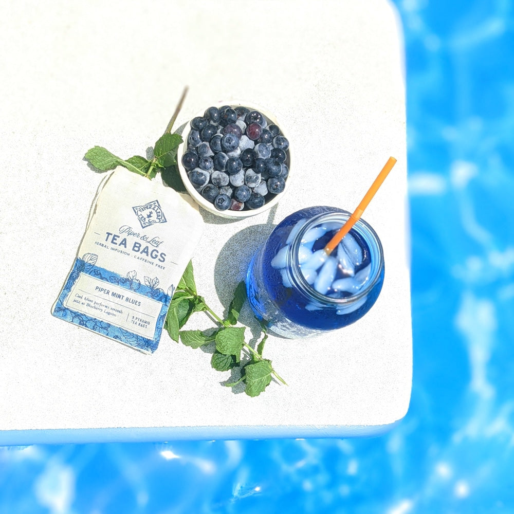 A top down view of an iced jar of Piper Mint Blues, its tea bags, a bowl of fresh blueberries, and a sprig of mint.