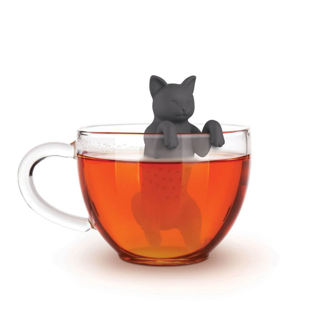 A cat shaped Fred-brand tea strainer in a glass teacup: Purr Tea