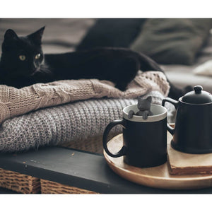 A black cat looks at a cat shaped Fred-brand tea strainer in a mug: Purr Tea