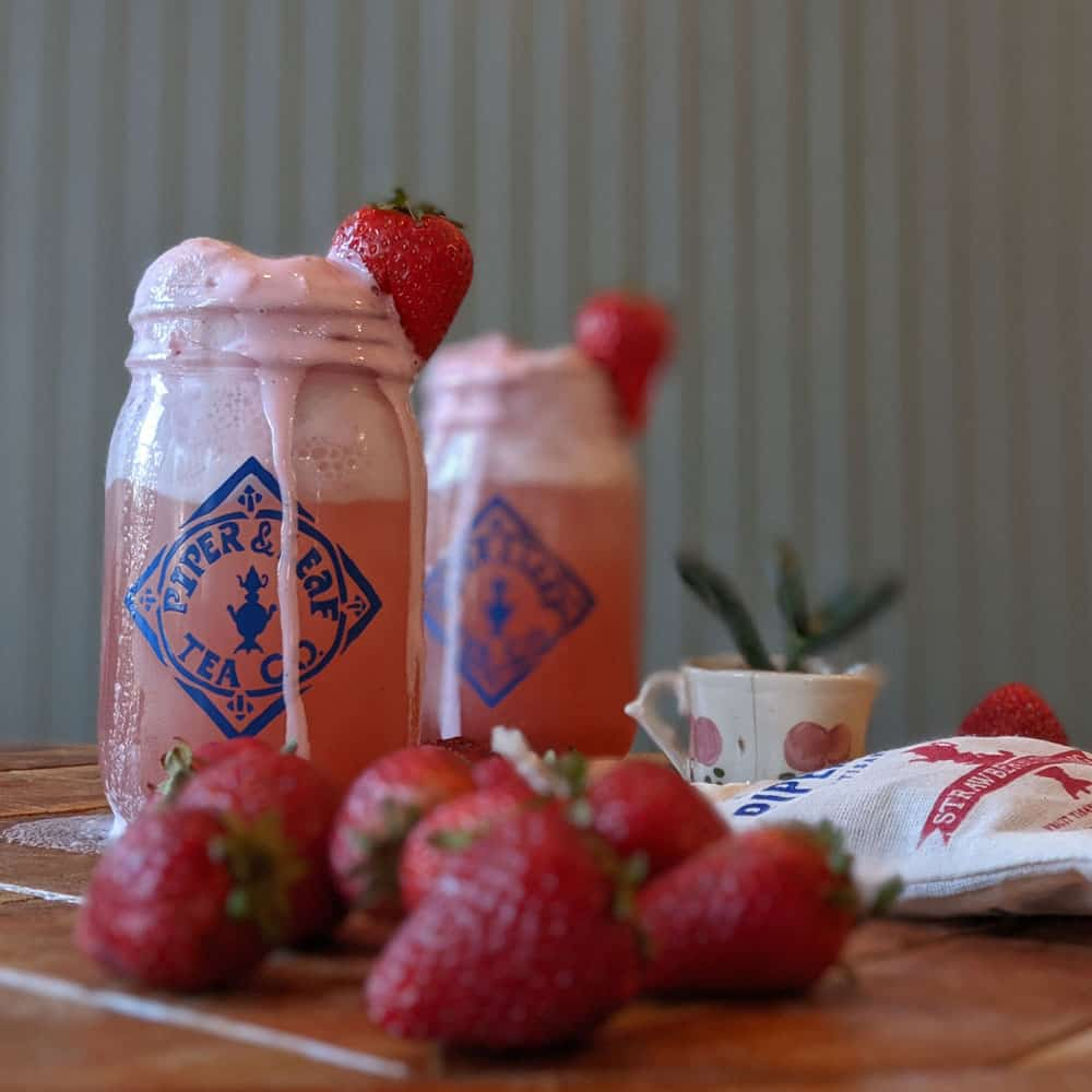 Pint mason jars with delicious sparkling Strawberry Shindig ice cream floats, surrounded by fresh strawberries