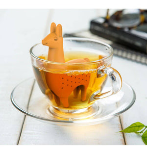 A llama shaped Fred-brand tea strainer in a glass teacup: Como Tea Llama