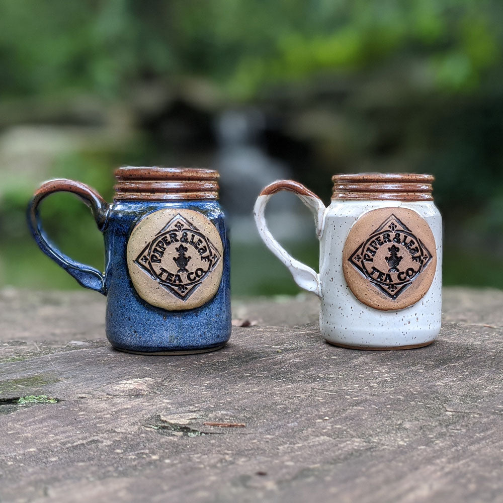 Hand-thrown pottery mugs with the Piper & Leaf logo. Two colors: blue and white