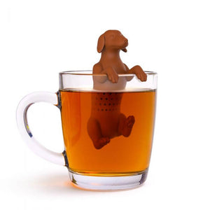 A dog shaped Fred-brand tea strainer in a glass mug: the Hot Dog