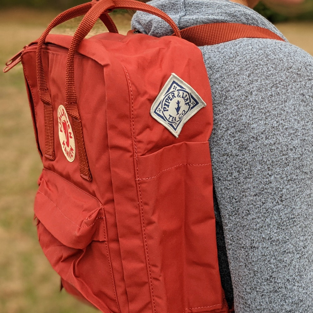 Side view of a red Fjällräven Kånken backpack with a sewn Piper & Leaf logo patch