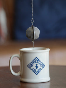 A tea ball strainer, full of loose leaf, being pulled out of a Piper & Leaf mug
