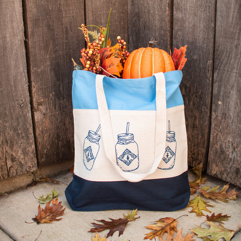 A tote bag printed with images of mason jars, filled with autumn decor and surrounded by fall leaves.