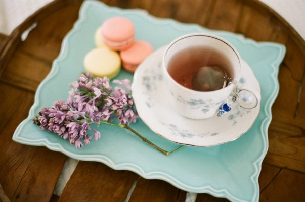 A blue tray holding macarons, fresh flowers, a teacup, and a saucer